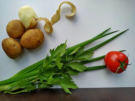 young potatoes next to freshly cut celery, tomatoes, green onion on a white table