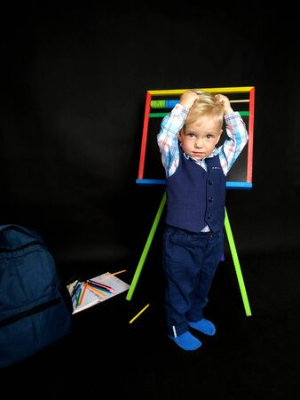 little boy in a blue suit holds his head while standing by the blackboard. back to school. Emotional boy. isolated on black