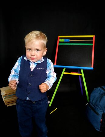 little boy in a blue suit frowns while standing by the blackboard. back to school. Emotions about back to school. isolated on black