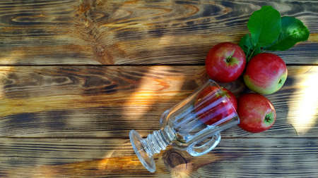 freshly picked apples in a transparent glass on a wooden background. apple juice or cider concept
