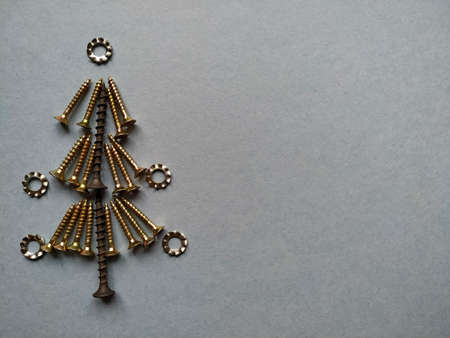 Christmas tree built of construction screws on a blue background.