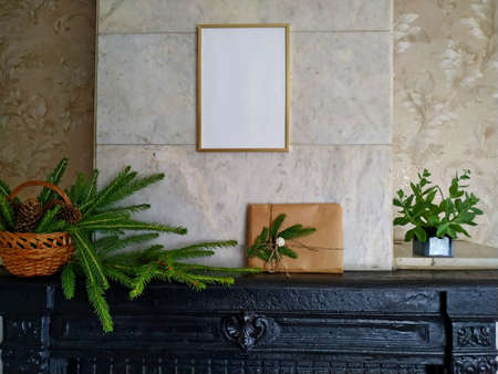 a christmas gift wrapped in craft paper and tied with linen thread on a mantelpiece next to fir branches in a wicker basket. Mock up over the fireplace with a christmas present and decoration Stock Photo