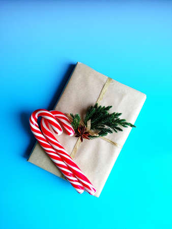 gift wrapped in craft paper, candy canes with small juniper branches. minimalistic christmas concept. Stockfoto