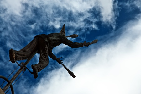 juggling: A statue that is juggling set against a dramatic blue sky