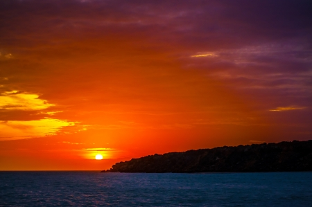 A spectacular purple, orange, and red sunset in Guajira, Colombia  photo