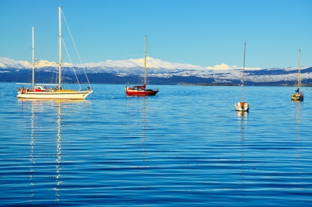 Boats in the Beagle Channel with snow covered mountains behind them