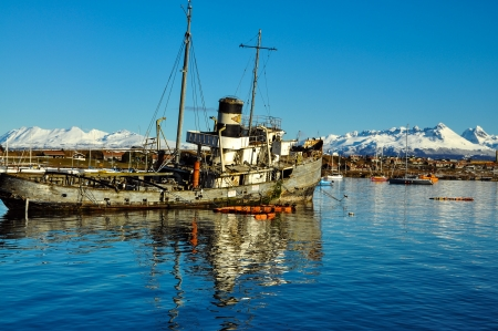 An old boat with Ushuaia and the mountains of Tierra del Fuego behind it