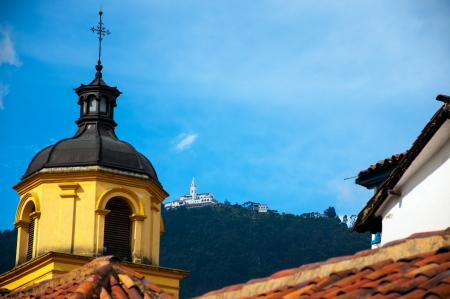 A yellow church in Bogota with Monserrate in the background  photo