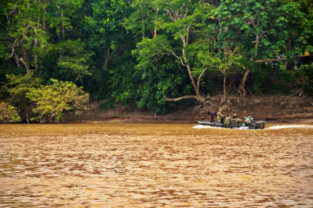 patrolling: La Macarena, Colombia - OCTOBER 2: Colombian military patrolling the Guayabero River