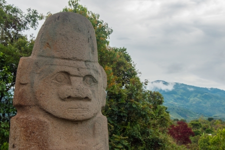 huila: An ancient statue with trees and hills behind it