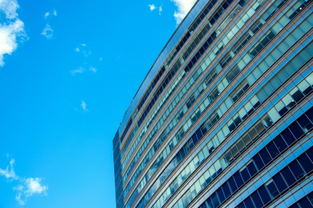 Details of a blue tinted office building against a beautiful blue sky
