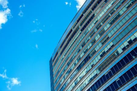 commercial real estate: Detalles de un edificio de oficinas tintado azul contra un cielo azul hermoso Foto de archivo