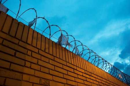 A yellow brick fence with barbed wire on top of it photo
