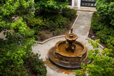 Beautiful fountain in green leafy courtyard photo