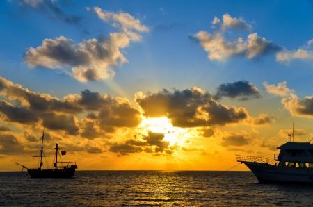 Blau und orange Sonnenaufgang über einem Piratenschiff in der Karibik in der Nähe von San Andres, Kolumbien