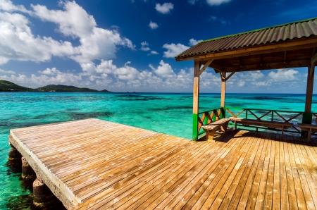 サン Andres y プロビデンシア島、コロンビアで美しいブルーとターコイズ色の水で木製のドック