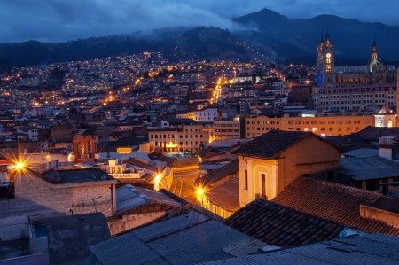ecuador: Quito, Ecuador old town and basilica at night with mountains in the background