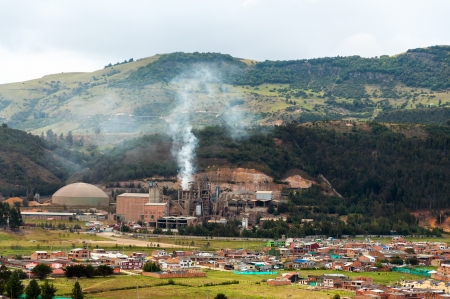 environmental issues: A factory producing pollution near a small town Stock Photo
