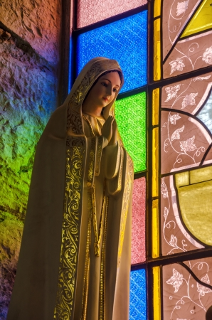 Virgin Mary statue with colorful stained glass in background in Choachi, Colombia