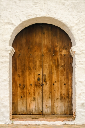 Wooden door on the side of a white colonial church photo