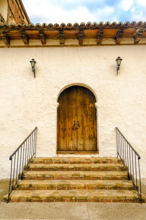 A wooden colonial door on the side of an old church photo