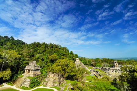 A wide view of Palenque featuring the main palace and several temples against a beautiful blue sky