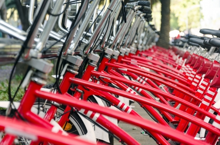 parked bicycles: Long row of red bicycles in Mexico City for public use Stock Photo