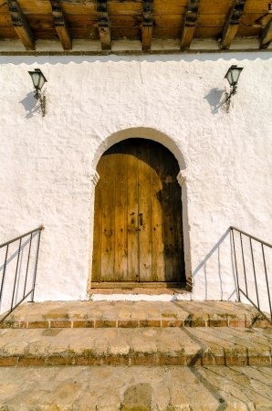 Old wooden door with white colonial wall photo