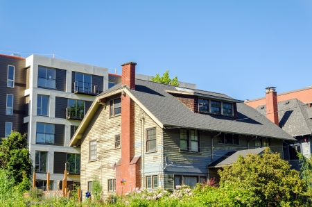Old dilapidated house in a neighborhood with nice stylish apartments in Portland, Oregon Stock Photo