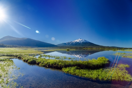Mount Bachelor being reflected in a lake with a lens flare near Bend, Oregon