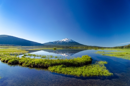 oregon  snow: A wide angle view of Mount Bachelor being perfectly reflected in a lake near Bend, Oregon