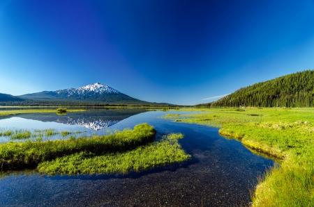 Mount Bachelor hetgeen tot uitdrukking komt in Sparks Lake gezien vanaf een weiland in de buurt van Bend, Oregon