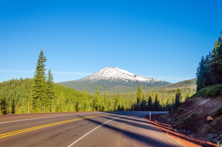 Curving highway with a dramatic view of Mt  Bachelor and beautiful green pine tree forest near Bend, Oregon