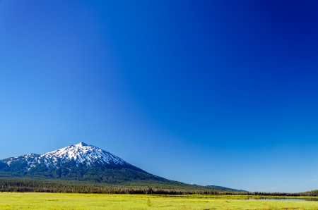 oregon  snow: Mount Bachelor seen from a green meadow with a deep blue sky in Central Oregon Stock Photo