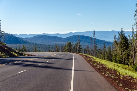 Highway curving through a dramatic nature scene in Central Oregon