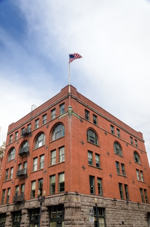 factory: Historic red brick building in downtown Portland, Oregon with the American flag waving high above it