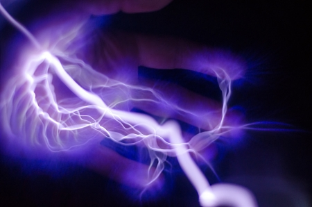 A hand with purple and blue lightning coming out of it photo