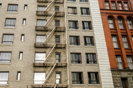 Two different color brick buildings, one with a fire escape running down the side of it in Portland, Oregon Stock Photo - 21392650