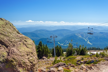 Chairlift going up Mount Hood with forest covered hills in the background and a large boulder in the foreground photo