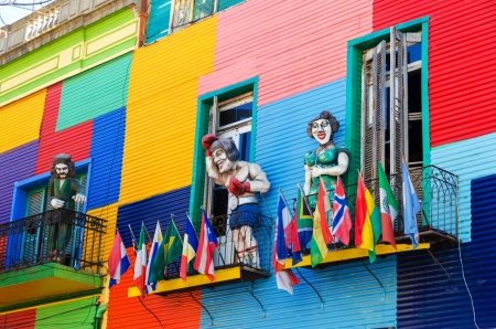 A colorful building in La Boca neighborhood of Buenos Aires with statues and flags