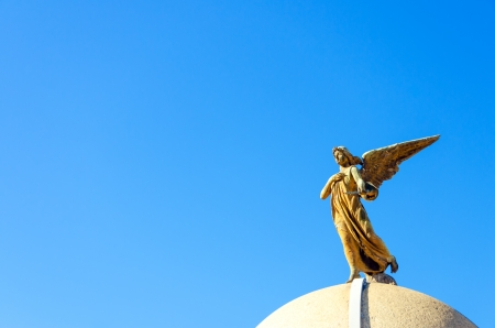 An angel on top of a tomb in the Recoleta Cemetery in Buenos Aires photo