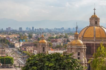 Oude Basiliek van Guadalupe met Mexico Stad skyline achter het Stockfoto