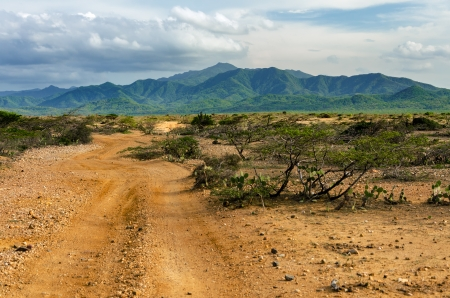 Dirt road passing through a desert with the lush green hills of Macuira National Park visible in the background in La Guajira, Colombia photo