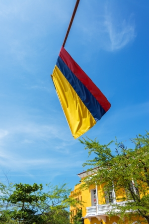 Colombian flag in the old town of Cartagena, Colombia with blue sky and colonial architecture photo