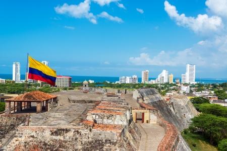 bandera de colombia: Vista del castillo de San Felipe de Barajas y el horizonte de Cartagena, Colombia, con una gran bandera de Colombia