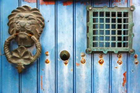 Old historic door knocker on a blue door in Cartagena, Colombia photo