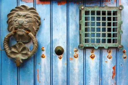 Old historic door knocker on a blue door in Cartagena, Colombia photo
