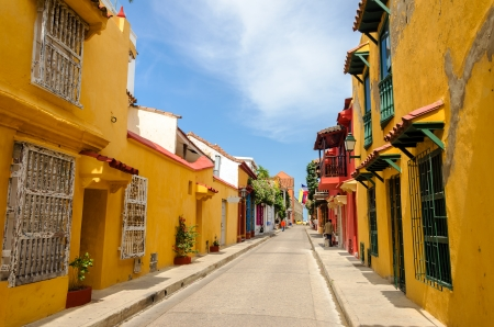 Typical street scene in Cartagena, Colombia of a street with old historic colonial houses on each side of it photo