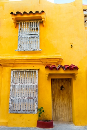 Windows and door of a yellow colonial building in the historic center of Cartagena, Colombia photo