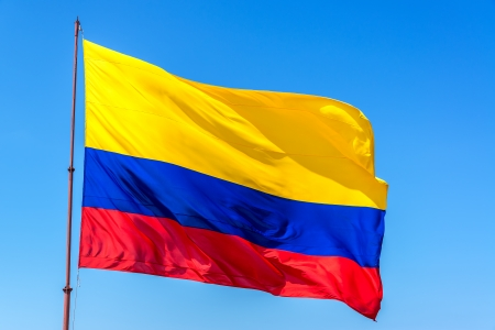 bandera de colombia: Bandera colombiana ondeando en el resplandeciente conjunto de viento en contra de un hermoso cielo azul